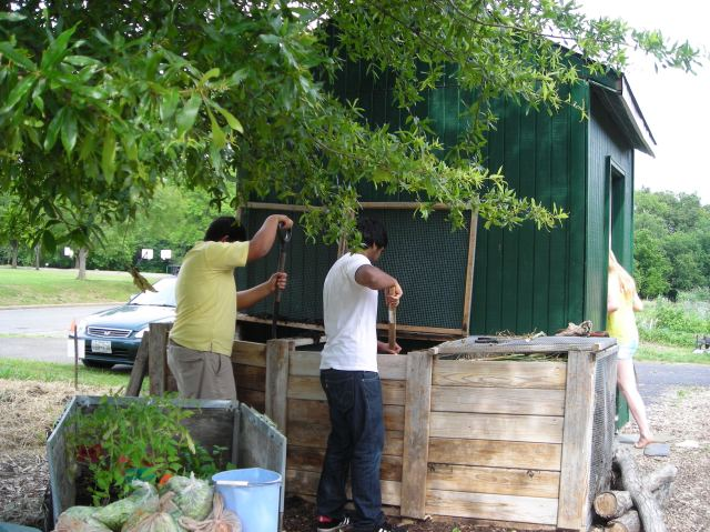 Students turn compost in bins before adding it to improve the soil of the organic vegetable beds at the T.C. Williams Discovery Garden.