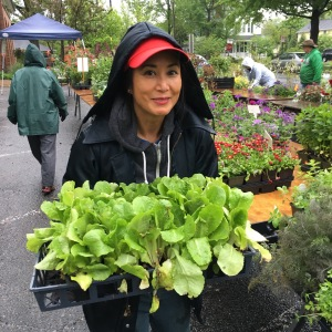 Intern Deanna Pineda smiling through raindrops and lettuce