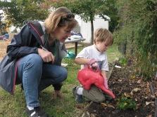 Master Gardener Susan Lewis with Carlin Hall Pre-Schooler, watering in the pansies