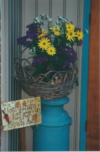 Blue milk can with basket of flowers and sign that says Gardeners don't grow old - they just Spade Away.
