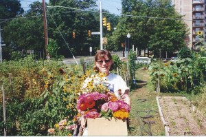 Carolyn Rapp holding flowers at the Barton Street Community Garden.